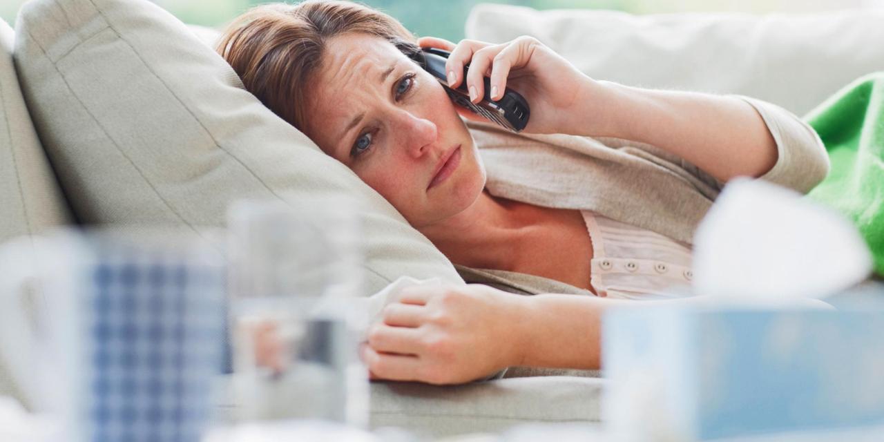 Sick woman laying on sofa talking on telephone.